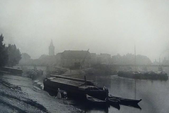 """Zdjęcie """"Mglisty poranek"""" pokazujące wylot Młynówki w 1895 roku. W tle wieża zamkowa."""