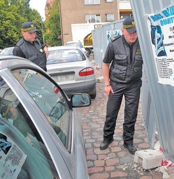 Strażnicy Miejscy kolejny raz sprawdzają, czy chyboczący się płot nie przewróci się na stojące tuż obok samochody. Lada dzień zostanie rozebrany, a w jego miejsce wybudowany nowy, dużo solidniejszy.