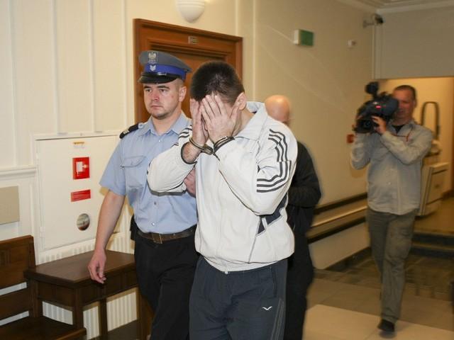 Oskarżony Aliaksandr M. zakrywa twarz