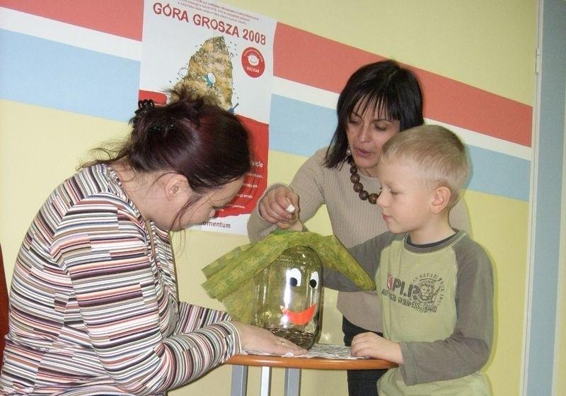 Joanna Kulasiewicz i Katarzyna Grzwyan z przedszkola numer 9. W środku przedszkolak Marcinek wrzuca swój grosik.