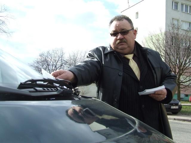 Polkowicki radny opozycyjny Ryszard Dyląg wkłada ulotki za szyby aut. Zapewnia, że rozbudowa parkingów przy ul. Wołodyjowskiego i Kmicica to jego zasługa
