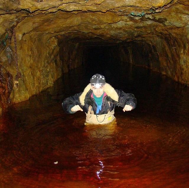 Część korytarzy jest pod wodą. Niektóre można przejść, inne trzeba przepływać pontonem. Na zdjęciu Paweł Grabowiecki z Głuchołaskiego Klubu Eksploracji.