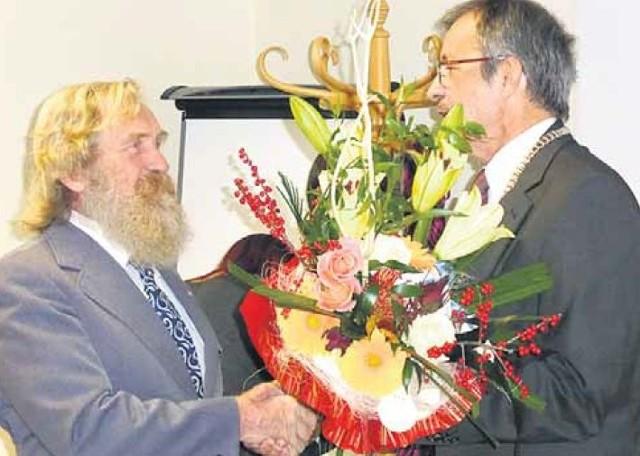 Przewodniczący Rady Miejskiej Witold Król wręcza kwiaty i składa gratulacje kajakarzowi w imieniu całego samorządu