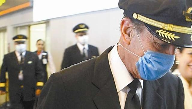 Załoga hiszpańskiego samolotu w maskach ochronnych opuszczała wczoraj lotnisko w Madrycie po przylocie z Meksyku.