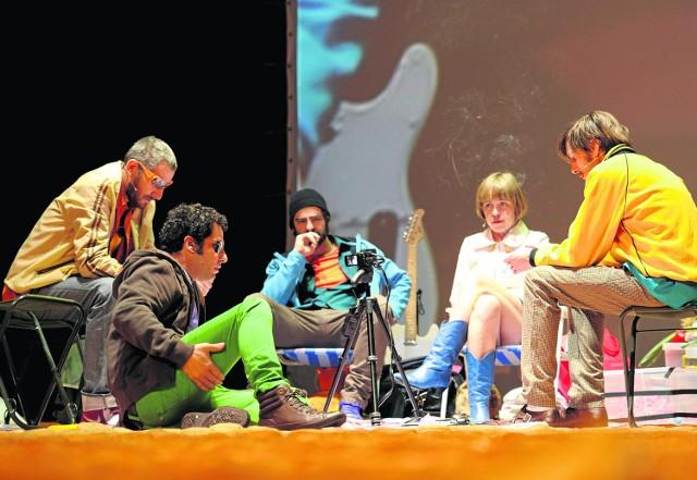 """Scena ze spektaklu """"Golgota Picnic"""". Aktorzy uczestniczą w pikniku na rozrzuconych hamburgerach i dyskutują..."""