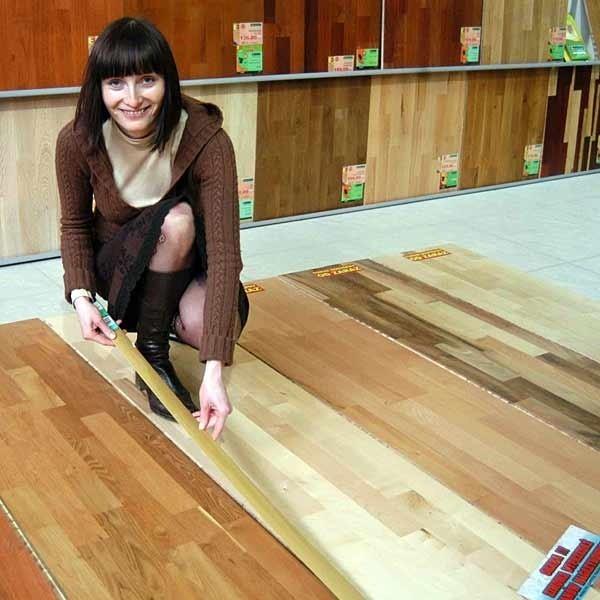 Anna Pastuszak, specjalista w rzeszowskiej firmie DANEX demonstruje jak można za pomocą ozdobnej listwy łaczyć różne podłogi.
