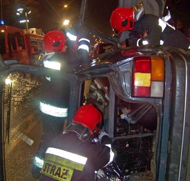 Strażacy ratują ofiarę wypadku samochodowego.