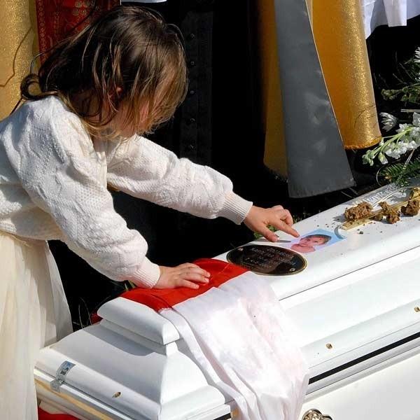 - Karolinka woła do nas: przestańcie czynić zło, uczyńcie świat przyjazny dzieciom - zaapelował w czasie pogrzebu ks. Piotr Rymarowicz.Na zdjęciu młodsza siostra żegna Karolinkę.