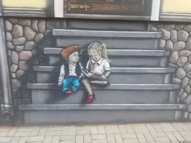 """Od kilku lat centrum Skwierzyny zdobią unikalne murale. Wydawałoby się, że takie klasyczne. Nie. Jak powiedział nam wiceburmistrz miasta nad Wartą, Wojciech Kowalewski, wzorem do murali były oryginalne kamienice, a raczej ich podobizny. Kamienice stały w tych miejscach, gdzie obecnie bloki. Tylko pogratulować pomysłu, i wykonania, bo chwilami aż chciałoby się do tych malowanych dzieci podejść, pogadać, no i wejść do takiej tajemniczej kamienicy.Wideo: Zielona Góra. Jakub """"BIKO"""" Bitka stworzył niesamowity mural poświęcony Wydarzeniom Zielonogórskim. 12.11.2020"""