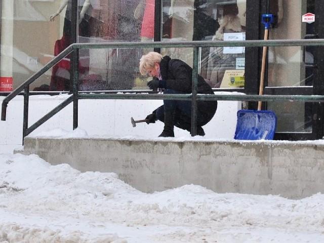 Po opadach marznącego deszczu we wtorek rano pracownicy sklepów w Tarnobrzegu skuwają lód przed wejściem do budynku.