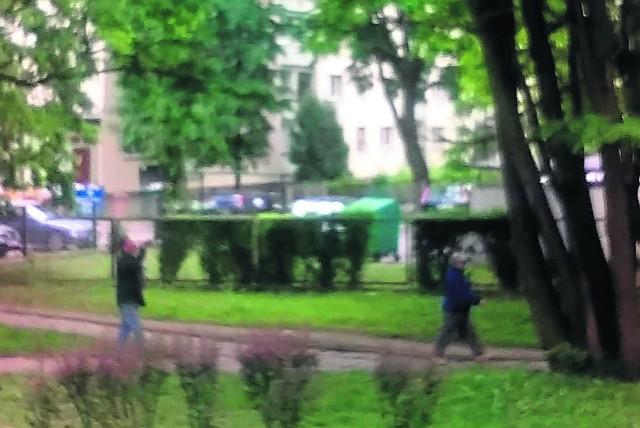 Ukryta kamerka: mężczyzna po lewej pije w biały dzień. W tle ogrodzenie przedszkola.