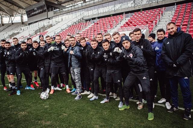 Bartłomieja Koperę (w okularach) wspierają piłkarze ŁKS