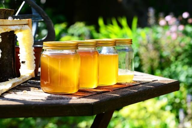 """Miód jest naturalnym płynem wytwarzanym przez pszczoły z nektaru kwiatów. Istnieje wiele różnych rodzajów tego produktu, w zależności od rodzaju kwiatów, z których powstaje. Jednym z najcenniejszych i zarazem najdroższych jest nowozelandzki miód manuka, który ma wyjątkowe właściwości lecznicze. Większość miodów dostępnych obecnie w sklepach to niestety podróbki, czyli produkty syntetyczne, które nie posiadają unikalnych i charakterystycznych dla prawdziwego miodu składników. Okazuje się, że także niektórzy pszczelarze dokonują """"zafałszowania"""" miodu, mieszając ten prawdziwy ze sztucznym. Jak wobec tego odróżnić miód naturalny od fałszywego? Jest na to kilka sprytnych sposobów. Wyjaśniamy, jakie cechy powinien mieć prawdziwy, naturalny miód."""