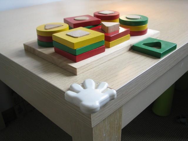 zabezpieczone narożniki stolika w pokoju dziecięcymTutaj maluch może sobie poszaleć! Narożniki stołu zostały zabezpieczone specjalnymi elementami, które przy okazji stanowią ciekawą dekorację pokoju dziecięcego.