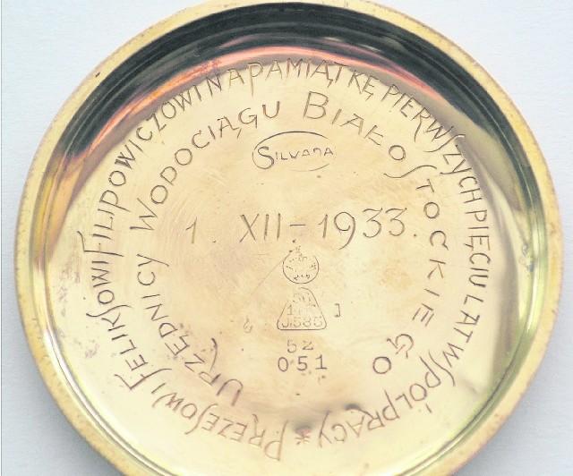Fragment koperty złotego zegarka z wygrawerowaną dedykacją. To jedna z niewielu osobistych pamiątek po Feliksie Filipowiczu, przewodniczącym rady miejskiej Białegostoku w latach 1919-1927. Zegarek przechowywany jest w Muzeum Podlaskim.