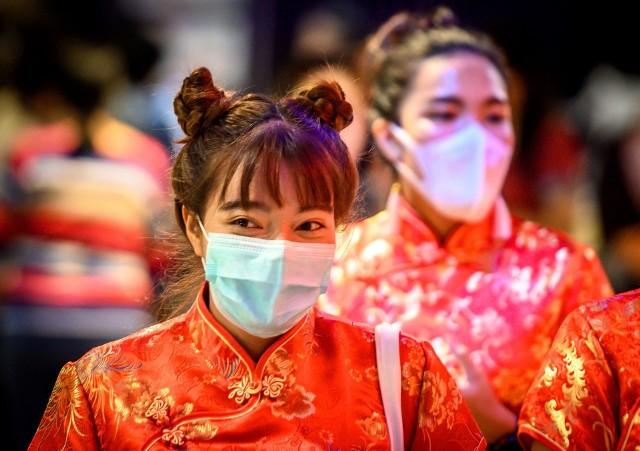 Kobiety noszą maseczki w sklepie udekorowanym z okazji księżycowego nowego roku.