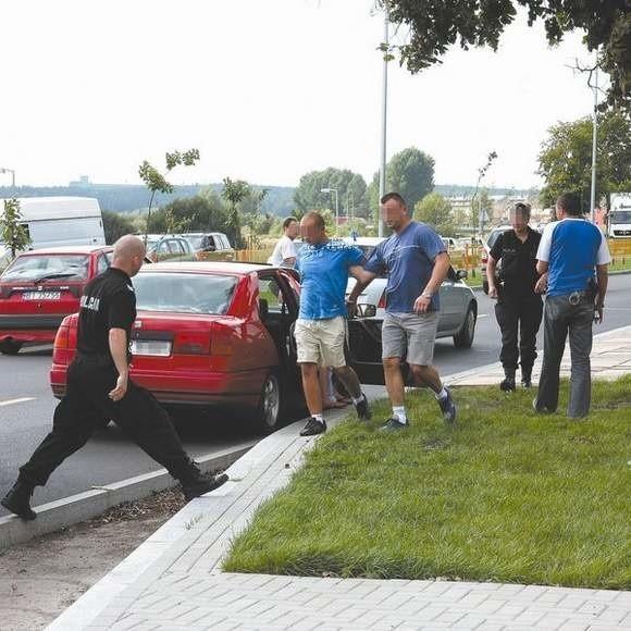 Policjanci skuli i położyli zatrzymanych na trawniku. Później poprowadzili ich do radiowozów.