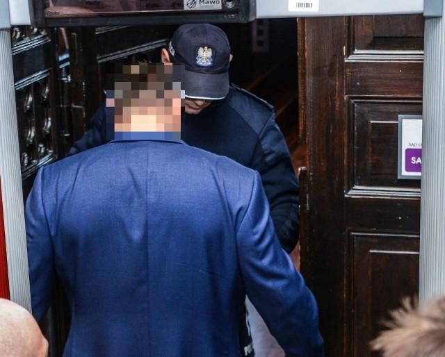 Tomasz B. kontrolowany przez policjanta przed wejściem na salę rozpraw. Gangster chce kary, ale zamierza uniknąć procesu
