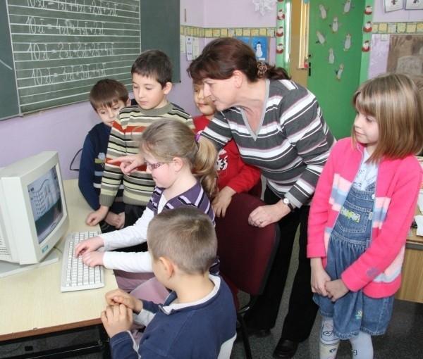 Nauczycielka klasy pierwszej Barbara Kopczak testuje z uczniami działanie sieci komputerowej. Od lewej: Tadeusz Wencel, Patryk Mitura, Kamila Skolny, przy komputerze siedzi Julia Walecko oraz  Łukasz Skolny i z tyłu stoi Julia Kupiec.