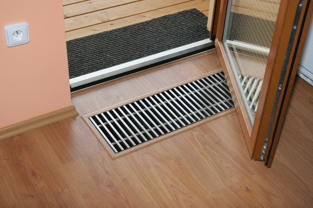 """Grzejnik kanałowy zamontowany przy wejściu na balkon.Dużą zaletą podłogówki jest dyskretny wygląd. Instalacja jest całkowicie ukryta pod podłogą. Nie wymaga konserwacji ani czyszczenia. Świetnie sprawdza się w pomieszczeniach, które narażone są na częste zabrudzenia podłogi, nanoszenie błota i wilgoci z dworu. """"Na pewno warto zastosować płytki i instalację ogrzewania podłogowego bezpośrednio przy wejściu, w łazience, w przedpokoju oraz w kuchni. W tych pomieszczeniach wygodna do mycia i szybko schnąca podłoga jest wielkim udogodnieniem, a brak grzejników pozwala dowolnie rozmieścić zabudowę szaf w przedpokoju i w kuchni"""" – doradza Marcin Kotas."""