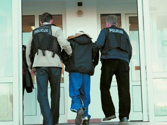 Policjanci prowadzą jednego z braci na przesłuchanie do prokuratury