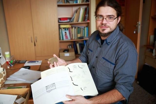 Adam Wawrusiewicz pokazuje zrekonstruowany z rozbitych fragmentów kielich