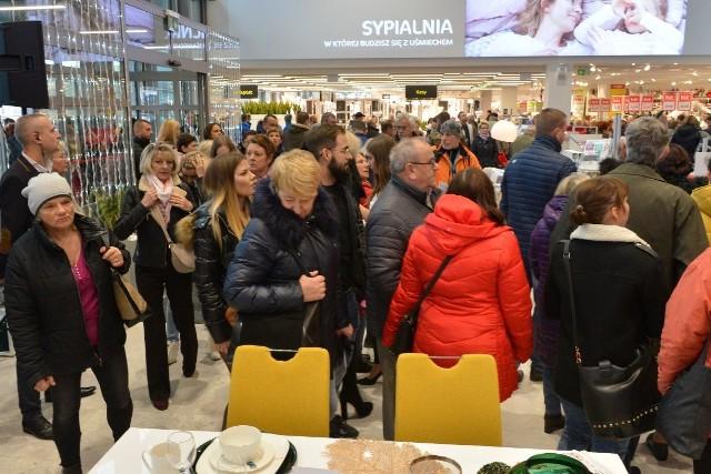 Setki osób pojawiły się w piątek, 22 listopada, na otwarciu salonu Agata Meble w Kielcach. Takiego oblężenia chyba nikt się nie spodziewał. Dla klientów przygotowano upominki oraz wyjątkowe promocje. ZOBACZCIE NA KOLEJNYCH SLAJDACH>>> Zobacz transmisję na żywo z tego wydarzenia: Już na pół godziny przed otwarciem salonu prawdziwe tłumy zebrały się przed budynkiem i z niecierpliwością czekały na godzinę 10. - Jest zimno – przyznała pani Alina, która przyjechała z mężem i ze swoją synową. - Szukamy jakiegoś ciekawego narożnika i stołu. Najlepiej w odcieniach brązu – przyznały panie.W końcu przyszedł czas na odliczanie do otwarcia. Gdy drzwi się rozsunęły do sklepu przez kilka dobrych minut wciąż wchodziły nowe osoby. Z okazji rozpoczęcia działalności salonu, na odwiedzających czekały upominki, a także specjalna, promocyjna gazetka. Klienci mogą skorzystać z atrakcyjnej promocji: rabat 10 procent na tysiące mebli i dodatków, a dodatkowo 60 rat 0 procent, trzy pierwsze raty gratis.- Witamy bardzo serdecznie. To 28 salon Agata Meble w Polsce. Przy wejściu proszę zaopatrzyć się w promocyjne gazetki, tym bardziej, że dwie z wymienionych promocji są ważne jeszcze tylko do końca weekendu – zachęcał prowadzący. - W naszej ofercie znajduje się ponad 20 tysięcy produktów. Agata to nie tylko meble, a także wszystko to bez czego nasze domy i mieszkania nie miałyby swojego charakteru. Mam na myśli dodatki, dywany, oświetlenie, tekstylia, porcelanę, szkło i wiele, wiele innych. Mówiąc krótko życzymy udanych zakupów – dodał.Obsługa salonu była do dyspozycji klientów. Chętnie doradzała, wyjaśniała wątpliwości oraz doradzała.Kielecki salon znajduje się przy ulicy Kongresowej 4 i jest jednym z największych salonów marki w Polsce pod względem powierzchni użytkowej. Na przestrzeni blisko 15,5 tysiąca metrów kwadratowych znajdą się meble oraz akcesoria do kompleksowego wyposażenia domu, jak również boksy z inspirującymi aranżacjami w wielu stylach wnętrzarskich.W nowym sklepie jednego z n