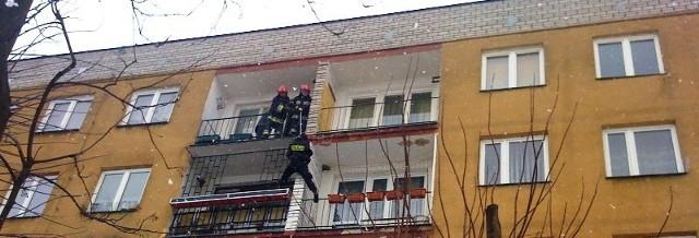 Strażacy i policjanci próbują się dostać do mieszkania zdesperowanej kobiety.