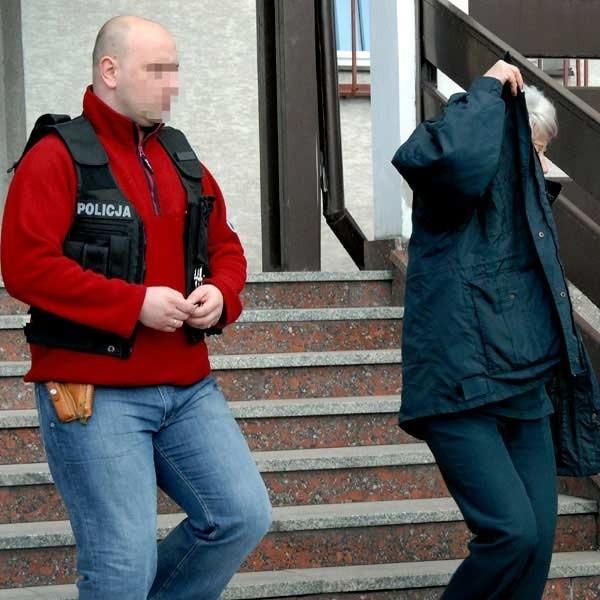 Jedna z zatrzymanych osób doprowadzana na przesłuchanie do prokuratury.