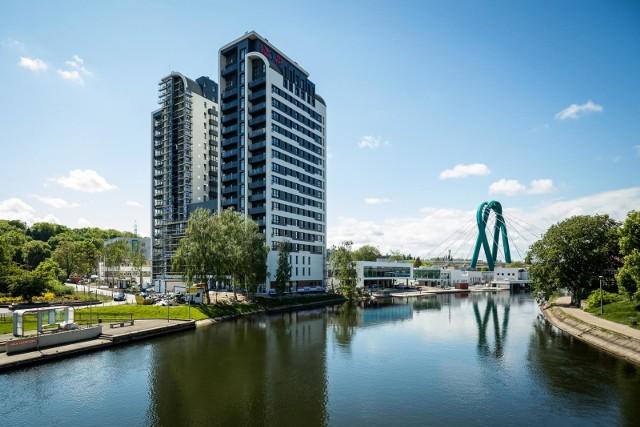 Zlokalizowany nad Brdą River Tower to obecnie najwyższy budynek mieszkalny w Bydgoszczy. Jego wysokość to 65 metrów. A jaką wysokość mają widoczne na drugim planie pylony Mostu Uniwersyteckiego? Sprawdź na kolejnych zdjęciach.
