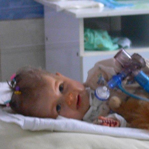Wiktoria w ostatnim dniu pobytu w szpitalu. Fotografię zrobiono przez szybę oddzielająca dziewczynkę od świata zewnętrznego.