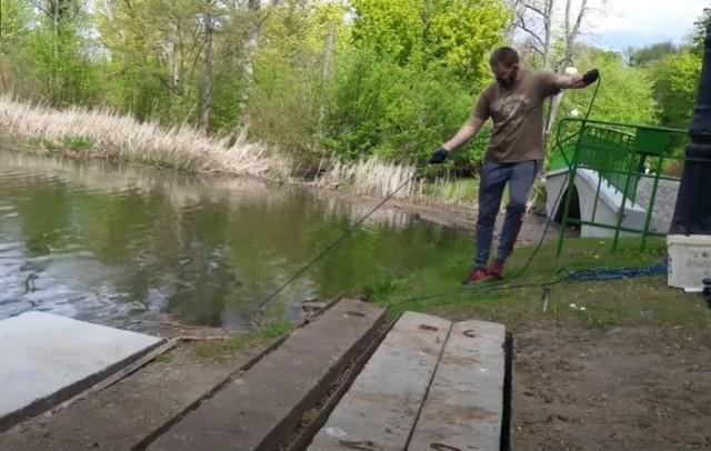 Łowienie złomu na stawach Sołackich - Marcin Nowakowski wykorzystuje magnes na lince