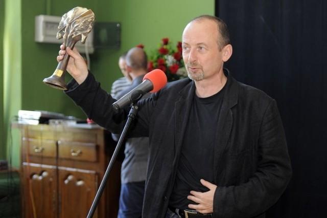 Paweł Łysak prezentuje nagrodę Nagrodę Ministra Kultury i Dziedzictwa Narodowego, którą odebrał w Warszawie.