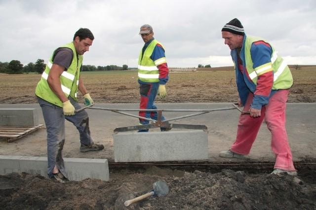 - Droga jest już prawie gotowa. Trzeba tylko wylać ostatnią warstwę asfaltu. My budujemy chodniki przy skrzyżowaniach w Pszczewie i Świechocinie - mówią (od lewej) Jacek Kolczyński, Janusz Ruman i Mirosław Bąbol z firmy Tombud.