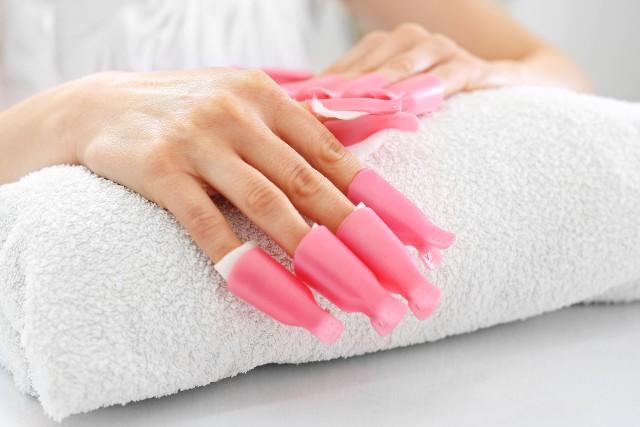 Coraz więcej kobiet zamiast regularnych wizyt u kosmetyczki wybiera własnoręczne wykonanie hybrydy. Sprzyja temu łatwa dostępność profesjonalnych urządzeń do zdobienia paznokci w zaciszu własnego domu oraz darmowe tutoriale w sieci. Wystarczy lampa UV, zestaw lakierów i kilka przydatnych środków, aby stworzyć oryginalny i tani manicure. Problem powstaje, kiedy znudził nam się kolor lub pojawił się odrost. Wówczas należy usunąć utwardzony lakier, starając się, by nie uszkodzić płytki paznokcia. Sprawdź, jak należy to zrobić!
