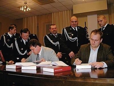 Wójt Zielonek Bogusław Król rozdaje egzemplarze zakupione przez gminę dla szefów jednostek OSP Fot. Barbara Ciryt