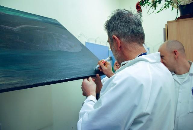 Pacjenci, lekarze i Wanda Ozierańska malują obraz w dyżurce lekarskiej.