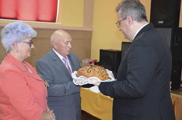 Jadwiga Balcerowska i Henryk Szczepański wręczyli chleb dożynkowy Piotrowi Gadzikowskiemu