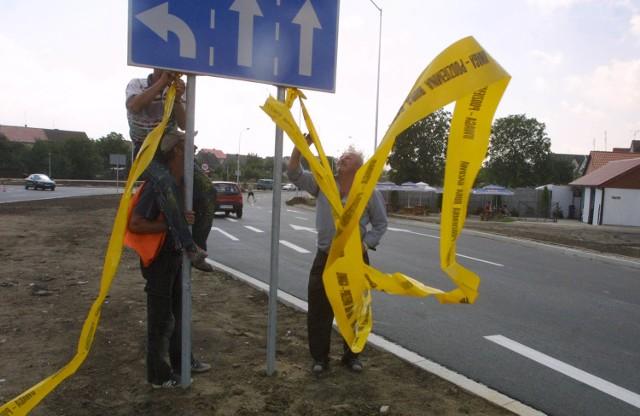 Zdejmowanie szarf ze znaków drogowych tuż przed puszczeniem ruchu ze skrzyżowania ulic Derdowskiego i Ku Słońcu w ulicę Europejską. Tuż po tym ulica Dworska, dotąd przelotowa, stała się ulicą lokalną.