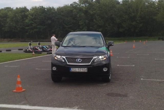 Mariusz Podkalicki, były kierowca rajdowy demonstruje slalom między pachołkami (test łosia) na lexusie hybrydowym RX450h.