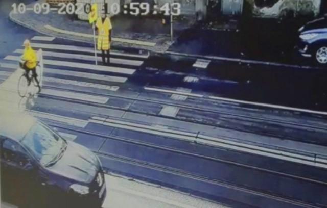 """Samochód przejeżdża przez przejście dla pieszych, gdy tzw. """"Agatka"""" pomaga przejechać na drugą stronę ulicy rowerzyście..."""