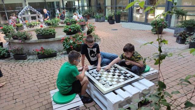 Nieco starsi czytelnicy miejskiej biblioteki mogą w odmienionym zielonym patio pograć w chińczyka czy szachy