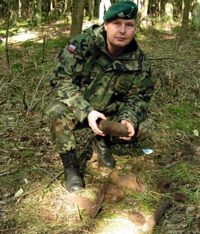 Dowódca pododdziału kompani saperów kapitan Mariusz Maciaszek prezentuje odłamki po pociskach.