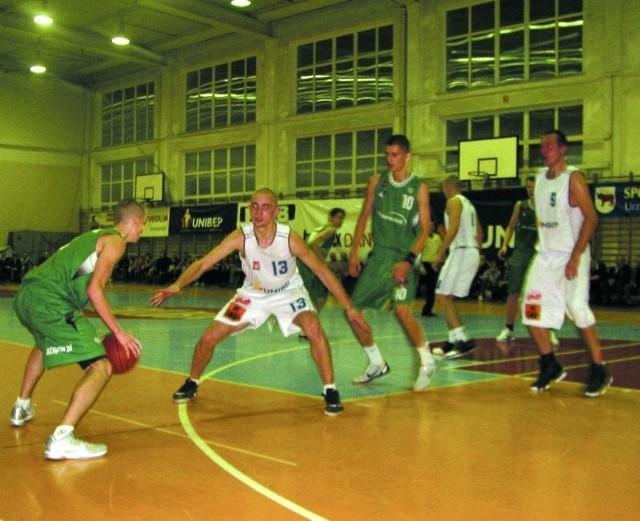 """Koszykarze bielskiego Tura (w białych koszulkach Mariusz Rapucha – nr 13 i Łukasz Kuczyński – nr 9) walczyli z młodszymi rywalami z Warszawy także w defensywie, ale znacznie lepiej wychodziły im ataki. – To była taka """"wesoła"""" koszykówka – przyznawali po meczu."""