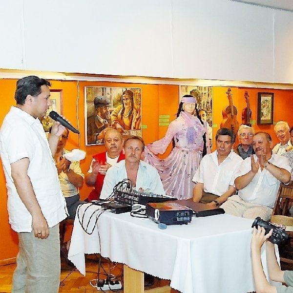 Na zdjęciu: Cezary Majewski (z lewej), w tle  wystawa poświęcona romskiej kulturze.