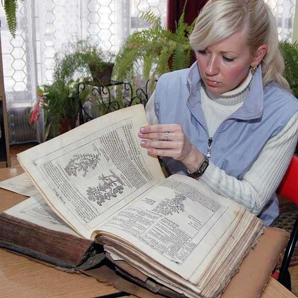 """Danuta Kalinowska z MNZP przy XVI-wiecznym ,,Zielniku"""", jednym z cenniejszych starodruków, które są własnością muzeum."""
