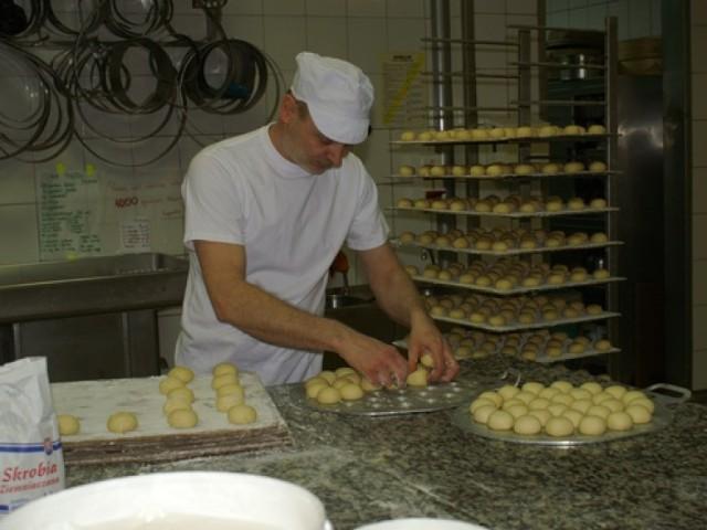Piekarz-cukiernik w Ciastkarni Kryszeń kręci ciasto na pączki i układa je na deski