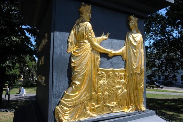 Postać z lewej symbolizuje Polskę. Obok niej jest tarcza z orłem bez korony