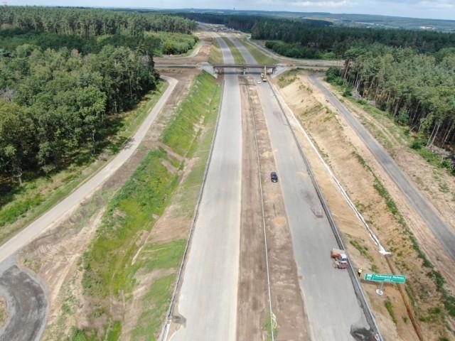 Letnia pogoda sprzyja prowadzeniu prac przy budowie ponad 14-kilometrowego odcinka drogi ekspresowej S3 pomiędzy Kaźmierzowem a Lubinem.    - Zaawansowanie robót na tym odcinku wynosi prawie 84 proc. Wykonawca kontynuuje prace związane z realizacją robót bitumicznych na drogach technologicznych i niektórych odcinkach trasy głównej.  Wykonywane są dowiązania do obiektów mostowych, gdzie wymieniane były dylatacje i ich naprawy zostały zakończone – informuje dolnośląski oddział Generalnej Dyrekcji Dróg Krajowych i Autostrad.    Przypomnijmy, że na placu budowy działa obecnie nowy wykonawca, który przejął niedokończoną inwestycję po włoskim konsorcjum, z którym została zerwana umowa.   Okazało się, że sporo elementów było wykonanych wadliwie i konieczne były naprawy. Wszystko jednak wskazuje, że w listopadzie ten odcinek trasy S3 zostanie udostępniony kierowcom.    W najbliższych dniach planowane jest betonowanie naprawionych już dylatacji oraz wykonywanie nawierzchni z asfaltu lanego na niektórych obiektach. Trwają prace wykończeniowe, m.in. montaż słupów i wypełnień ekranów akustycznych oraz barier.   Na węzłach i MOP-ach montowane są oprawy oświetleniowe. Trwają prace związane z wykańczaniem zespołów oczyszczających na kanalizacji deszczowej. Zakończono budowę zbiorników retencyjnych i przebudowę rowów melioracyjnych, w tym cieku Moskorzynka.   Pod koniec sierpnia wykonawca rozpocznie układanie nawierzchni na trasie głównej.   Wideo: Droga S3 w Lubuskiem