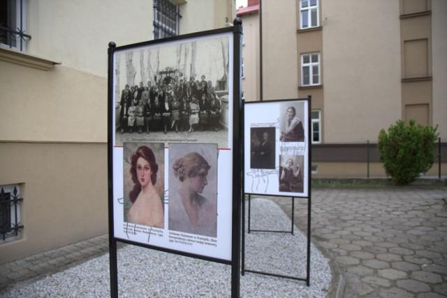 Plenerowa wystawa starych fotografii z fryzurami kobiet i mężczyzn, przed budynkiem Archiwum Państwowego w Przemyślu.